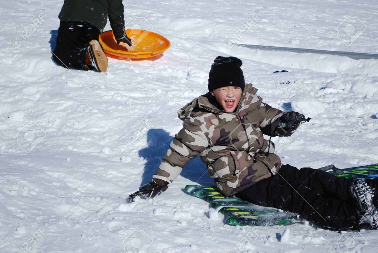 252566e18 Young boy sitting on a sled in the snow outdoors.