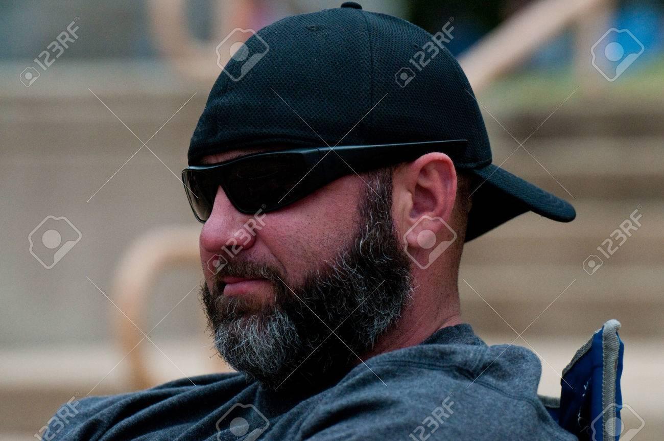 vendite speciali vasta gamma di offrire Uomo di mezza età con la barba nera e grigia indossando occhiali da sole e  cappello all'indietro.