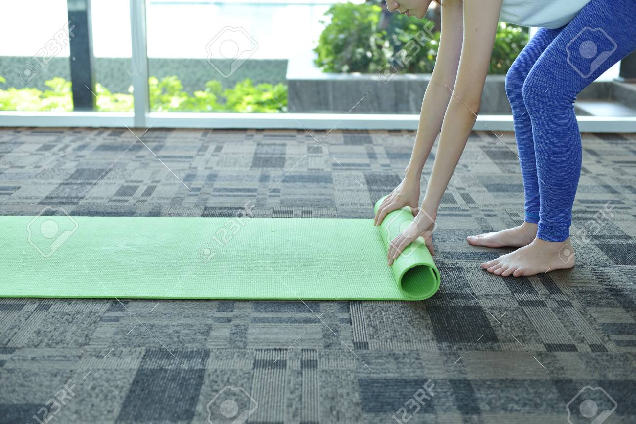 989f46bef484 Young Woman Rolling Mat After A Yoga On Carpet Floor