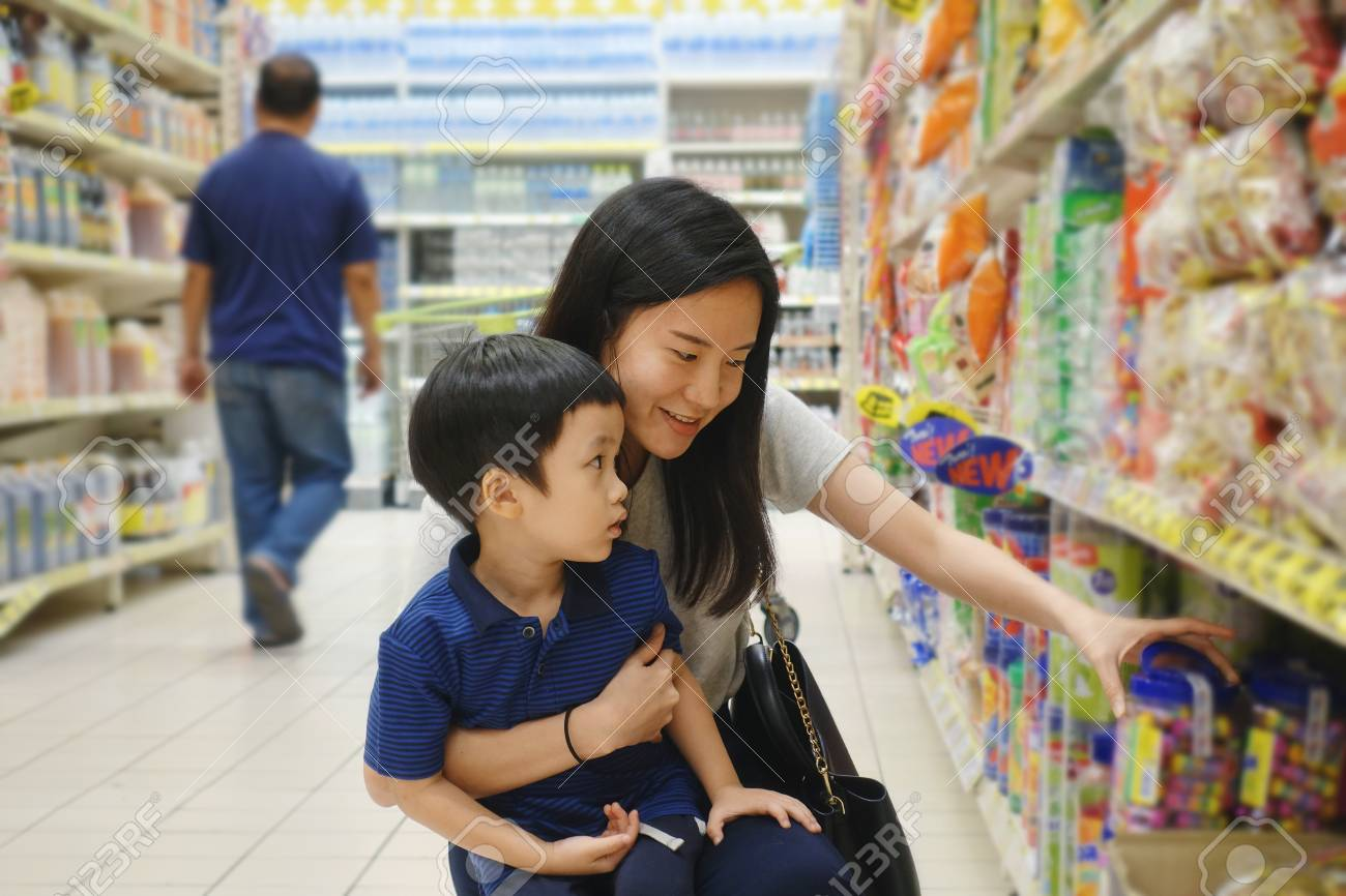 Young Asian mother and her kid shopping in supermarket with blurry background - 95649349