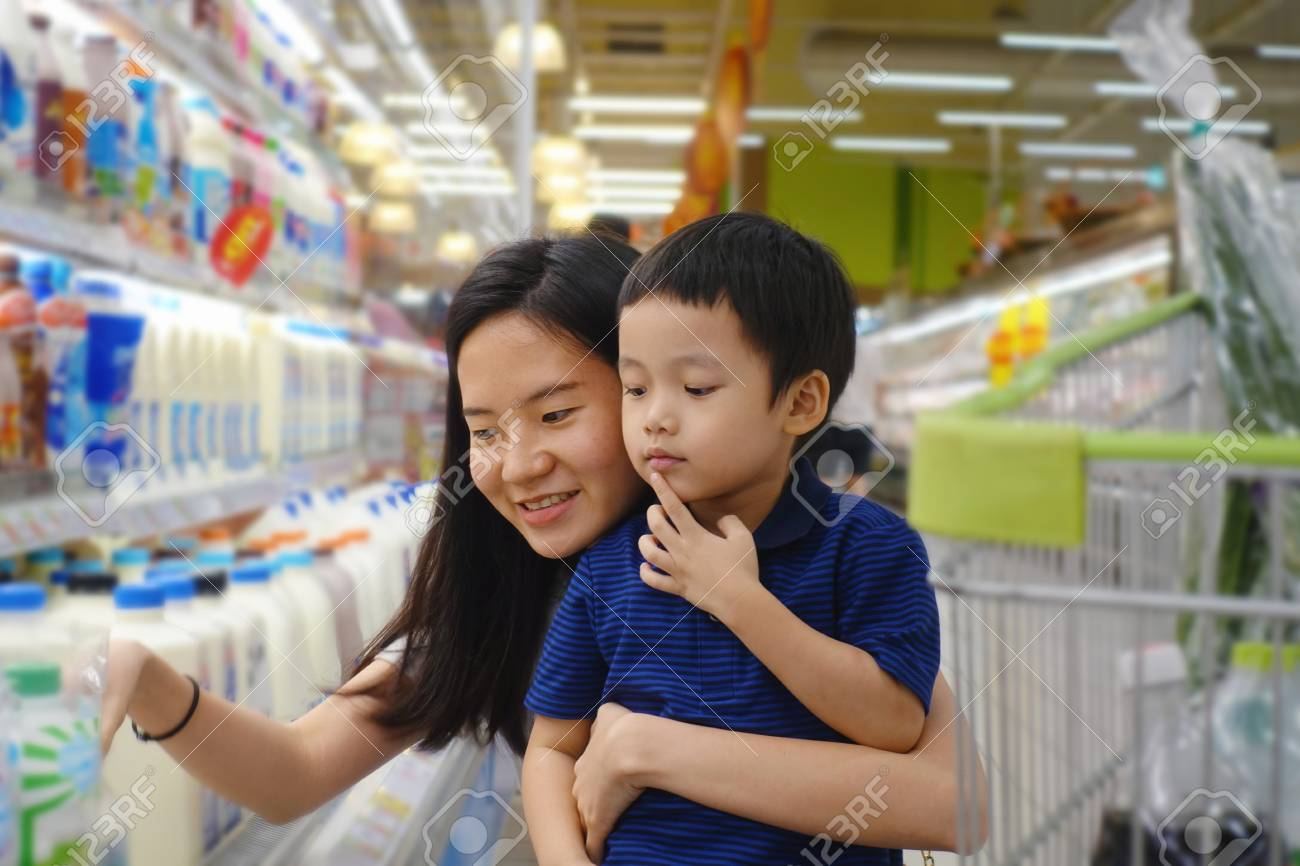 Young Asian mother and her kid shopping in supermarket with blurry background - 95603560