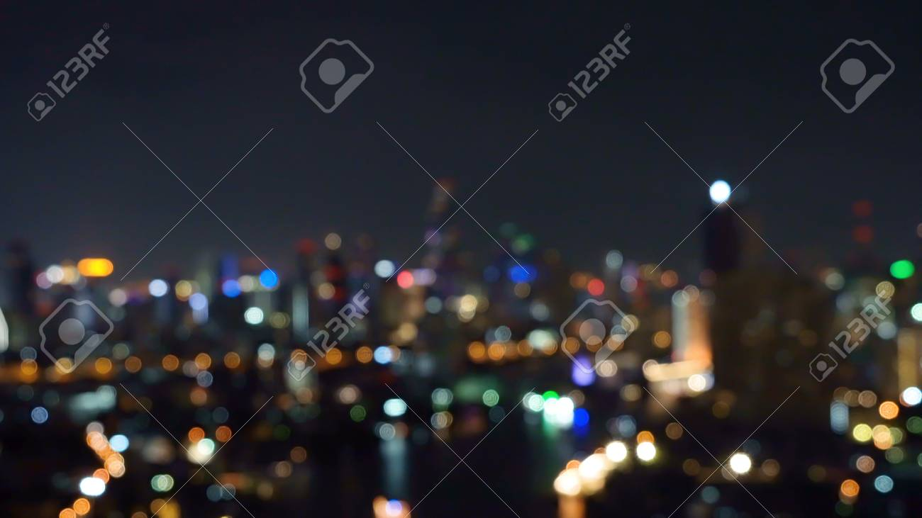 Bokeh background of skyscraper buildings in city with lights, Blurry photo at night time. Cityscape - 124873569
