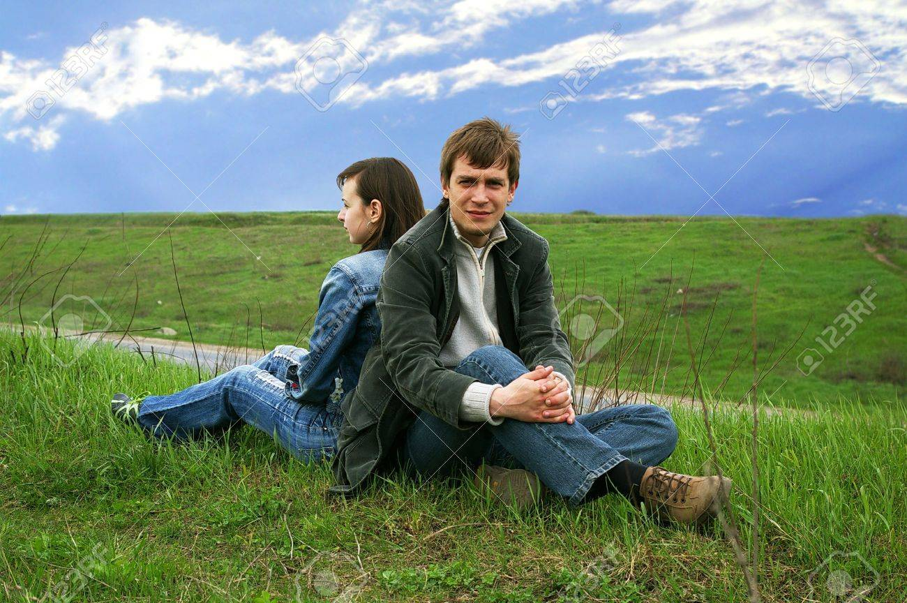Guy and girl sits on a grass on a background of the sky Stock Photo - 2904233