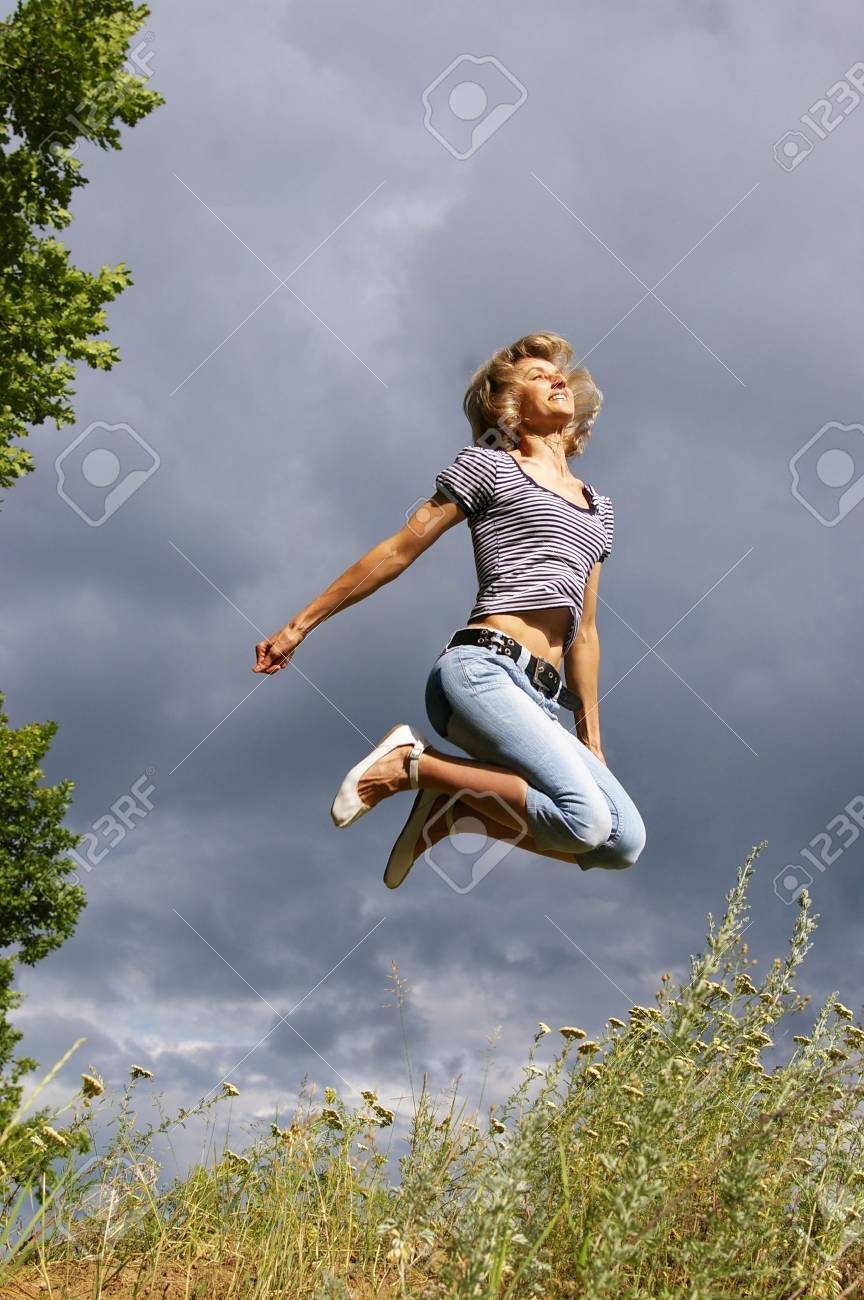 Beautiful young woman jumps. Sky as background Stock Photo - 3295083