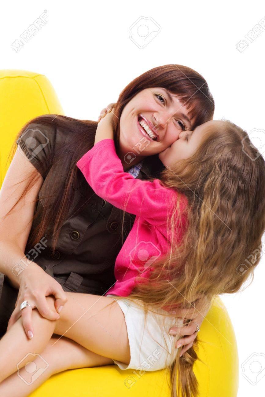 Cute little girl kiss her smiley mother. Studio shot Stock Photo - 5852189