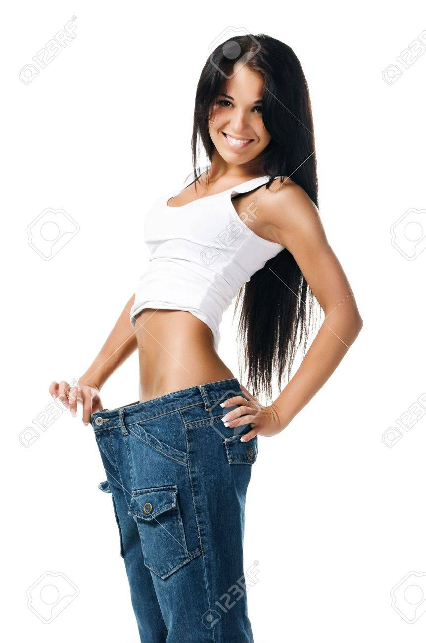 Woman demonstrating weight loss by wearing an old pair of jeans Stock Photo - 7803490