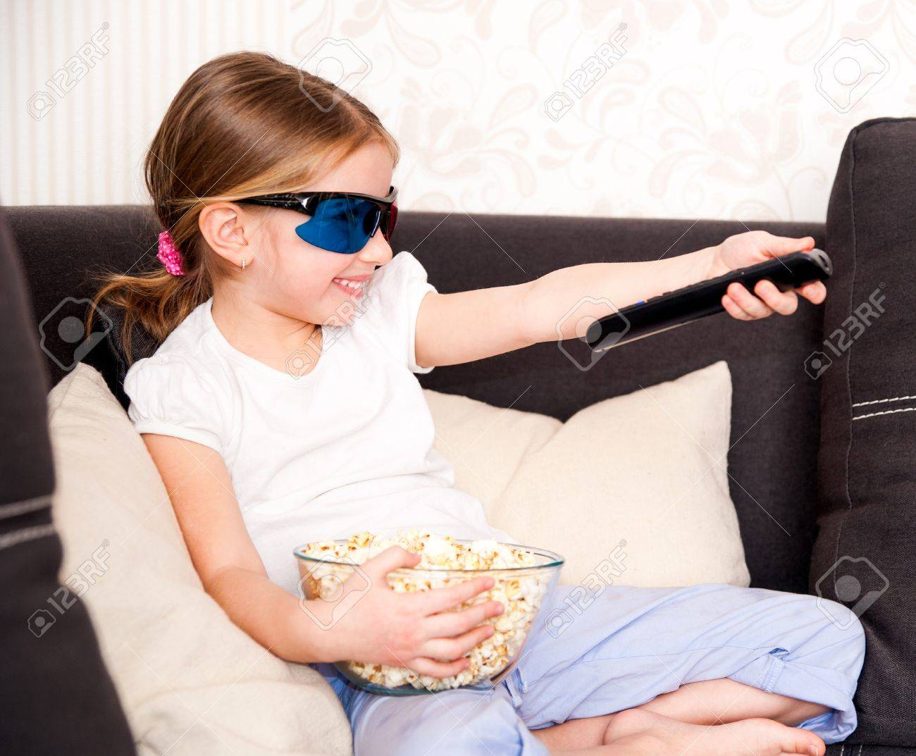 little girl with popcorn in 3D glasses holding a remote control Stock Photo - 18627093