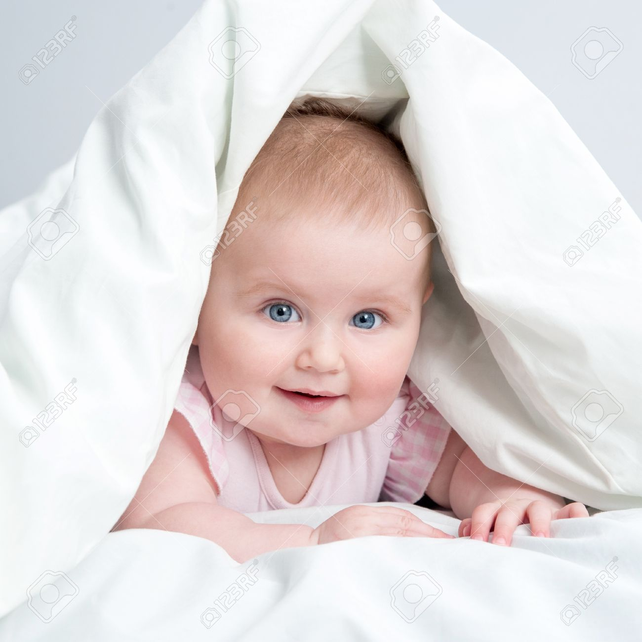 Cute Baby Under A White Blanket In Bed Stock Photo   19662094