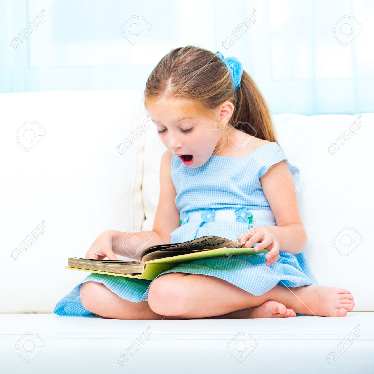 little cute girl reading a book and siting on the sofa stock photo