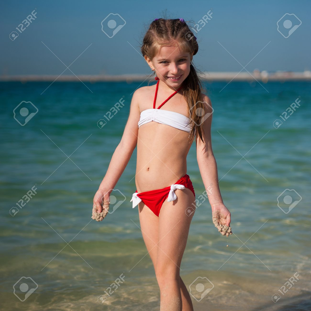 cute little girl in red-and-white swimsuit on the beach stock photo