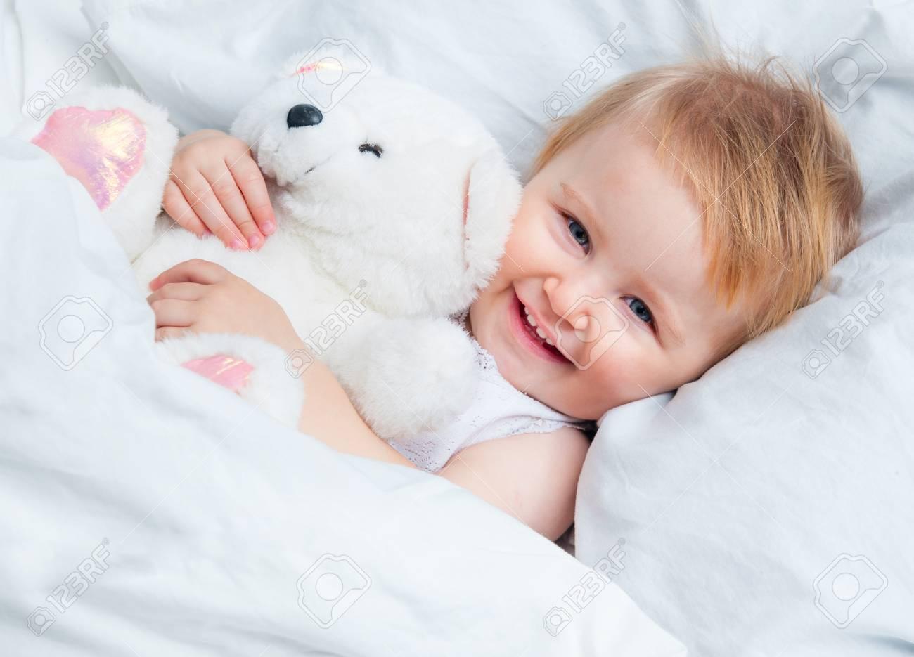 Hermoso Bebé Con Un Juguete Del Oso De Peluche En La Cama Blanco ...