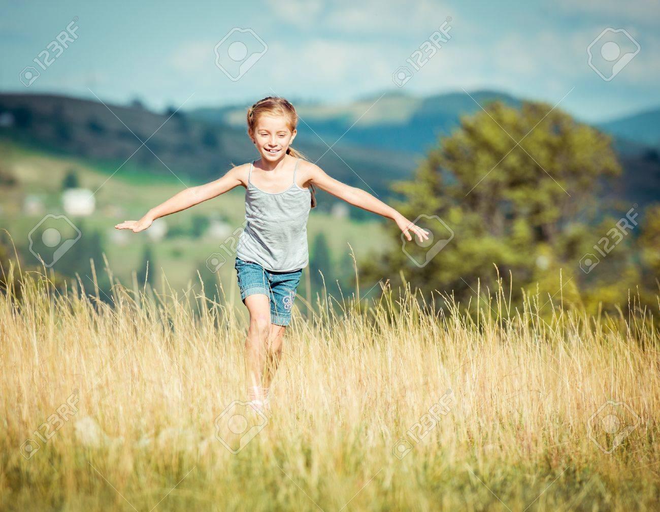 little girl runs through a beautiful meadow - 32217597