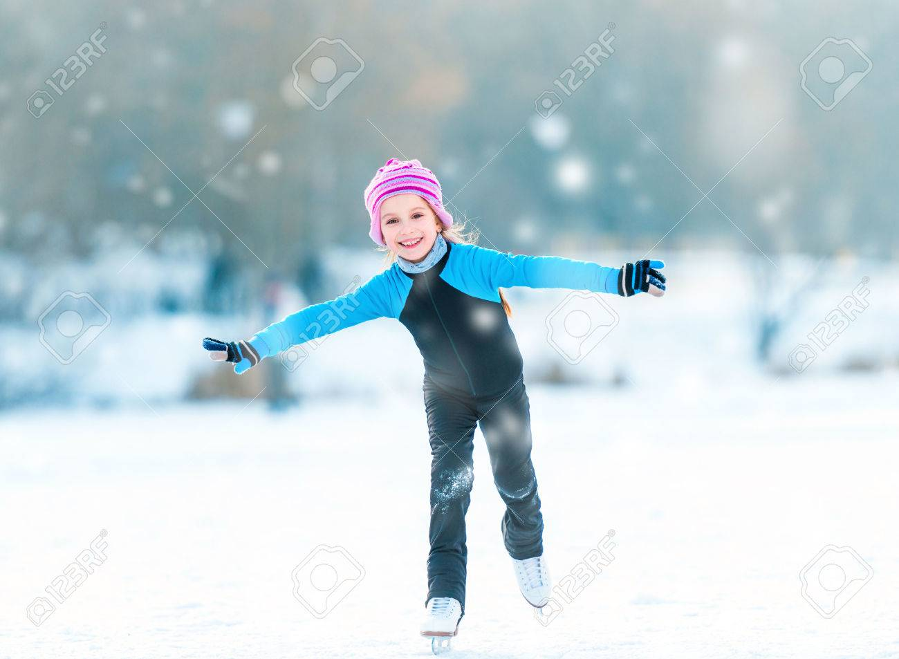 pretty cheerful little girl in thermal suits skating outdoors - 32218391