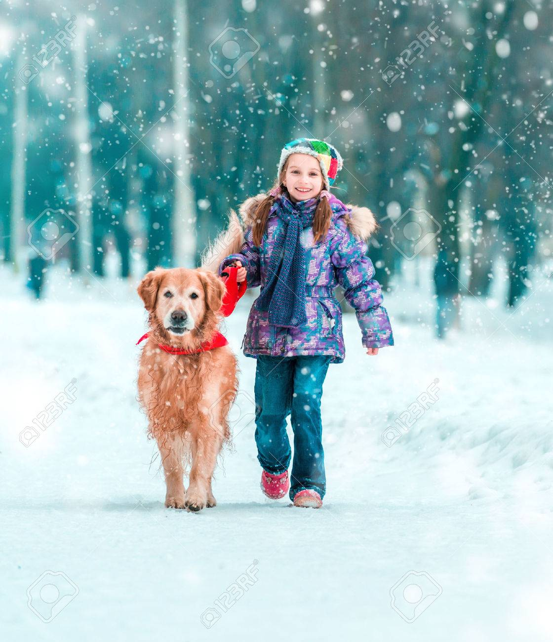 beautiful little girl with her dog on the snow in winter - 32251949