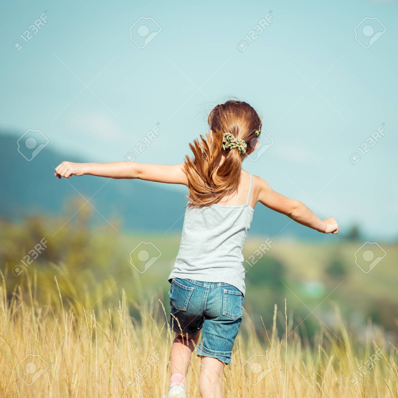 little girl runs through a beautiful meadow in the mountains. back view - 32252064