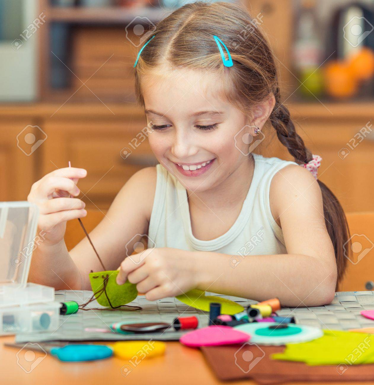 happy cute little girl is engaged in sewing - 33880879