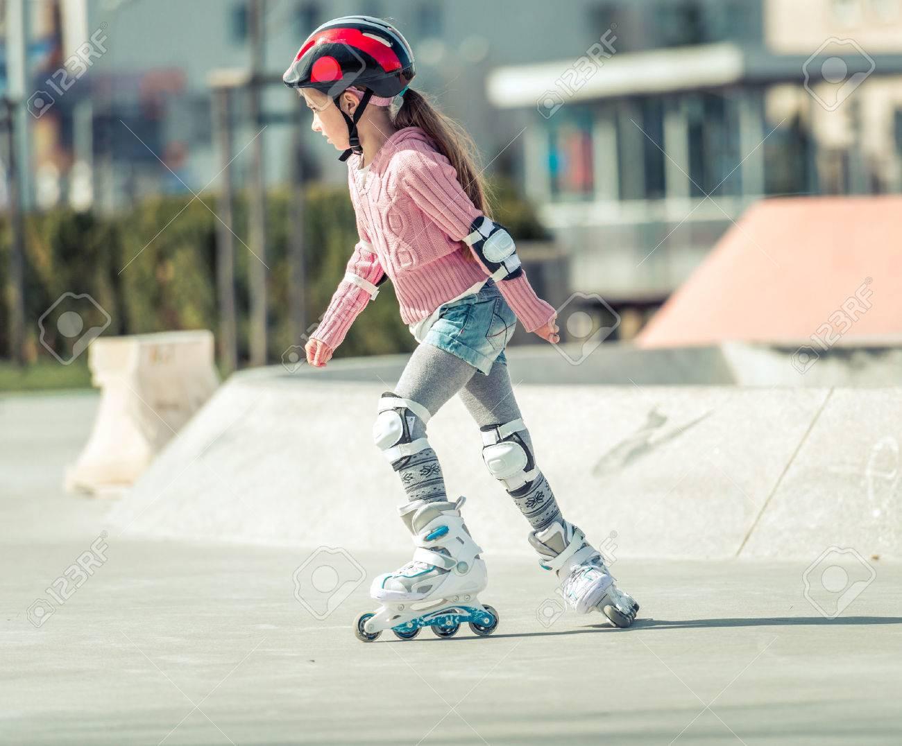 Little pretty girl on roller skates in helmet at a park - 39465915