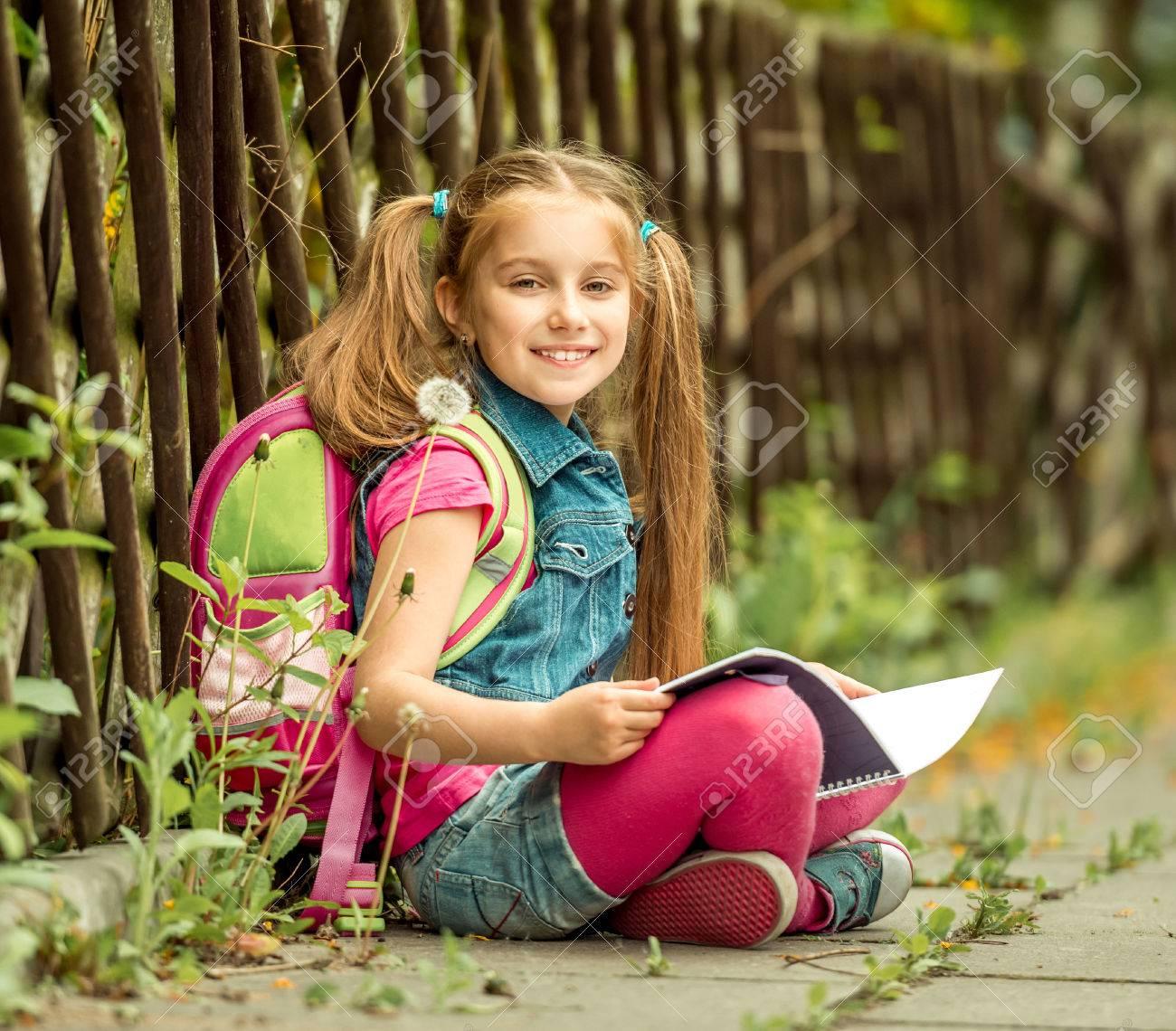 Little pretty schoolgirl reading a book sitting on the street - 40854476