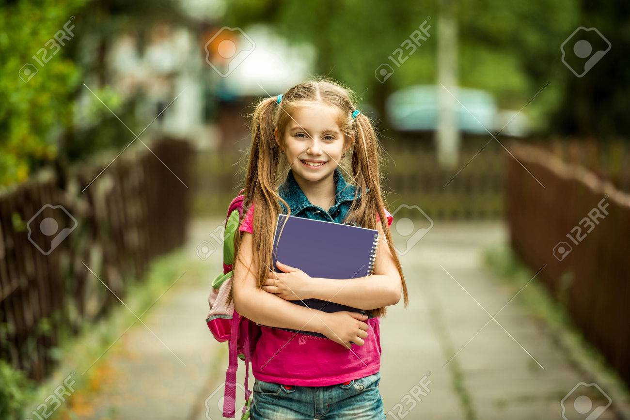 Little pretty schoolgirl with the book on the street - 40854480
