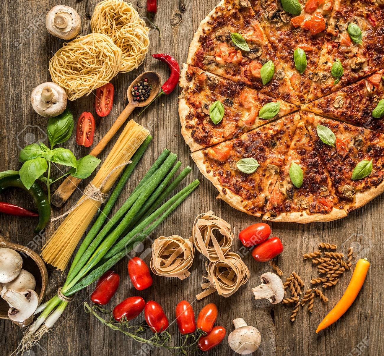 Italian food background with pizza, raw pasta and vegetables on wooden table - 41510281