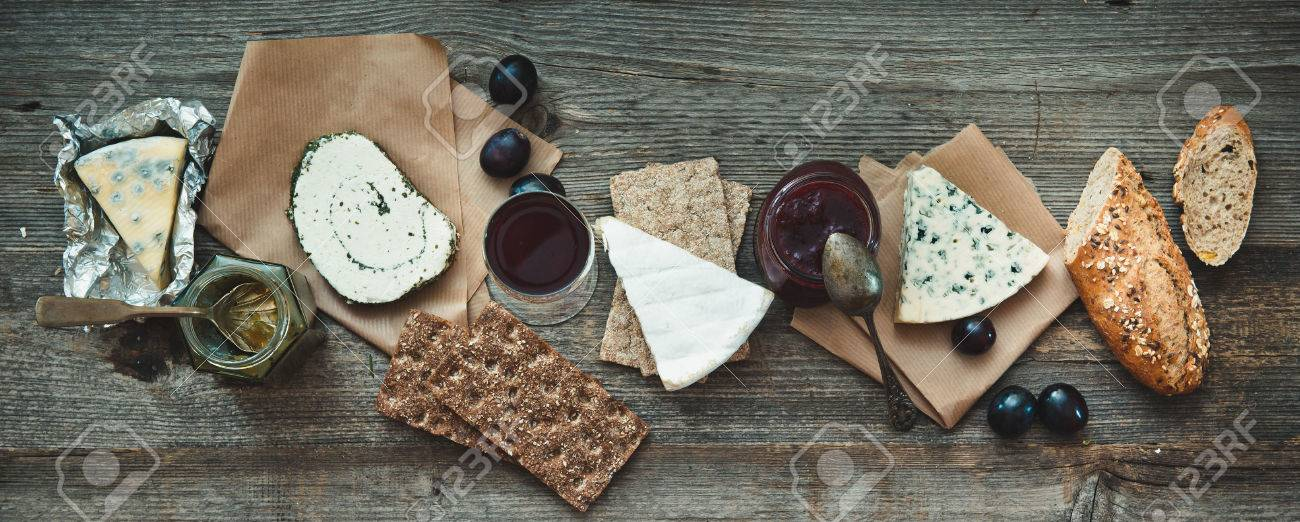 French food on a wooden background. Different types of cheese, wine and other ingredients on a wooden table - 43021487