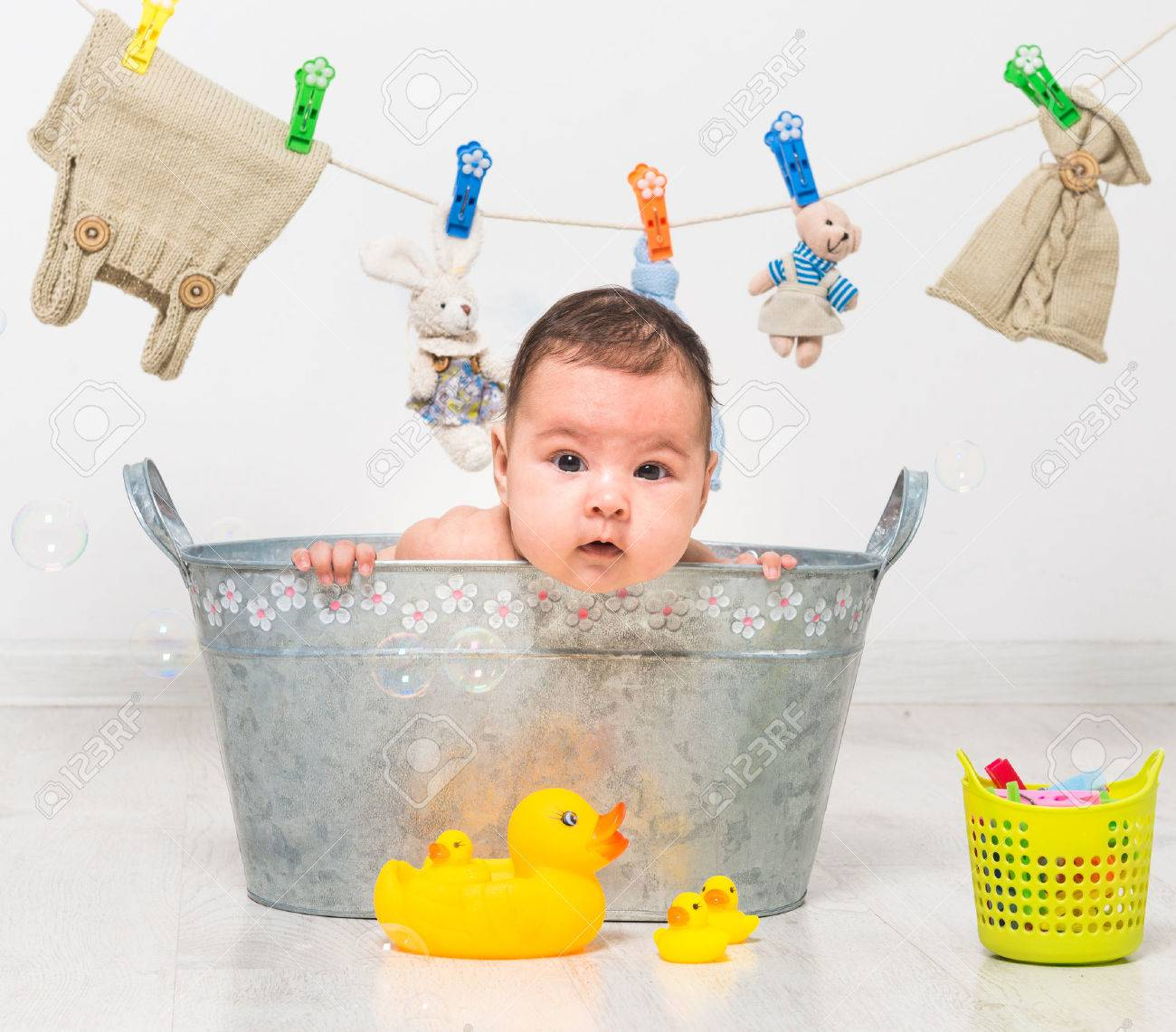 little two-month girl bathes in a trough and dry her clothes - 43286437