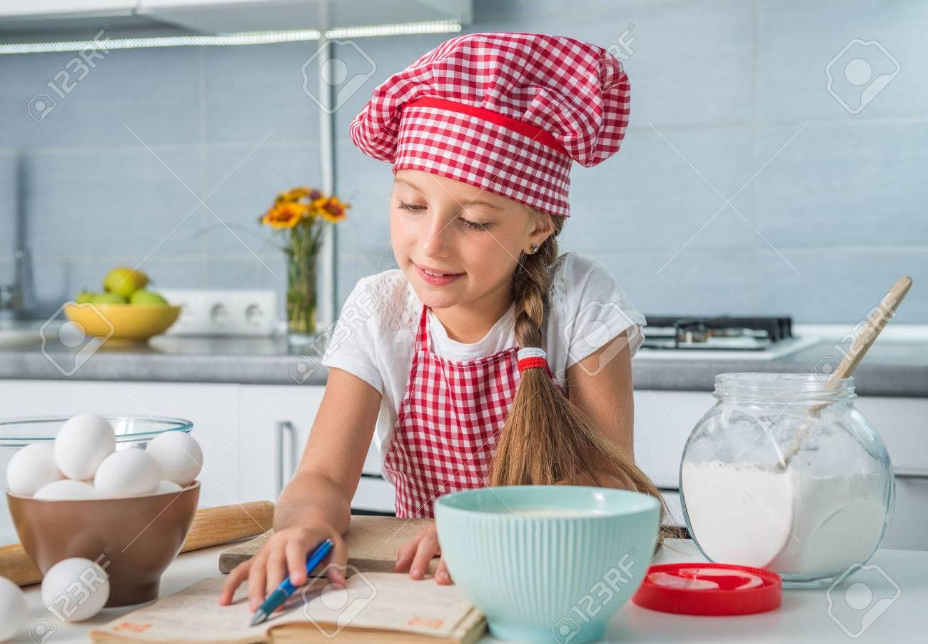 little girl baker reading a recipe on kitchen - 43785620