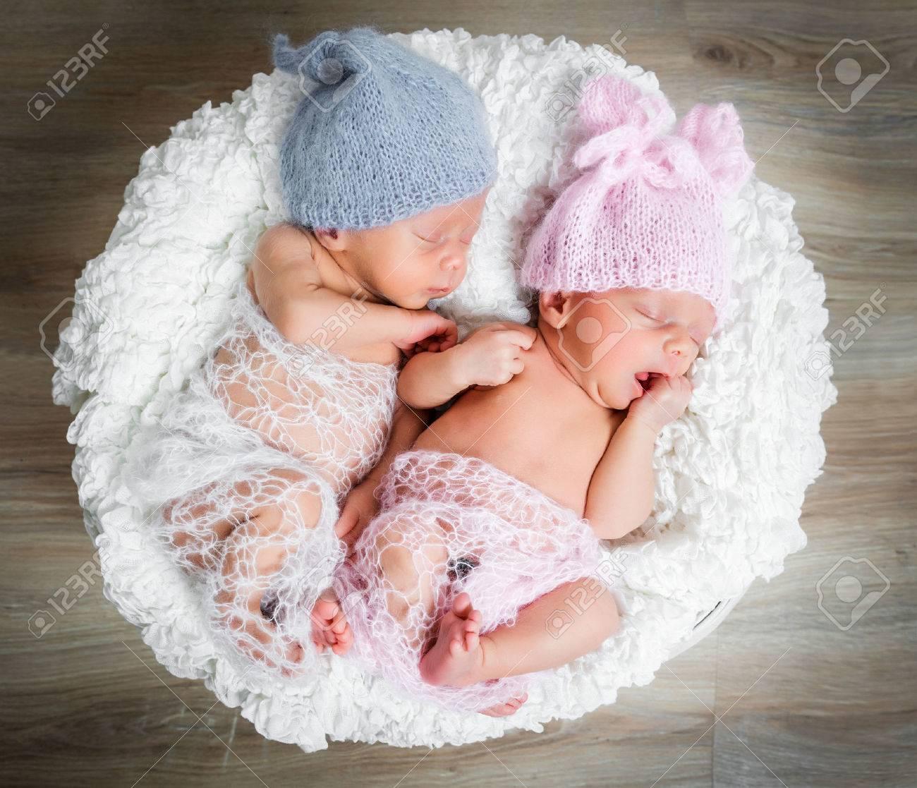 newborn twins - a boy and a girl sleeping in a basket - 43785640