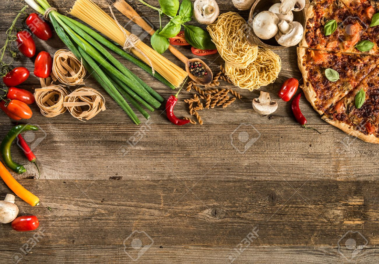 Italian food background with pizza, raw pasta and vegetables on wooden table - 44144439