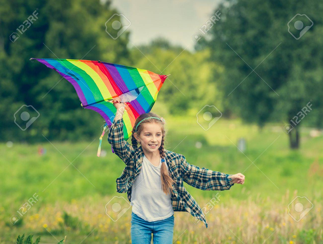 little cute girl flying a kite in a meadow on a sunny day - 44481331