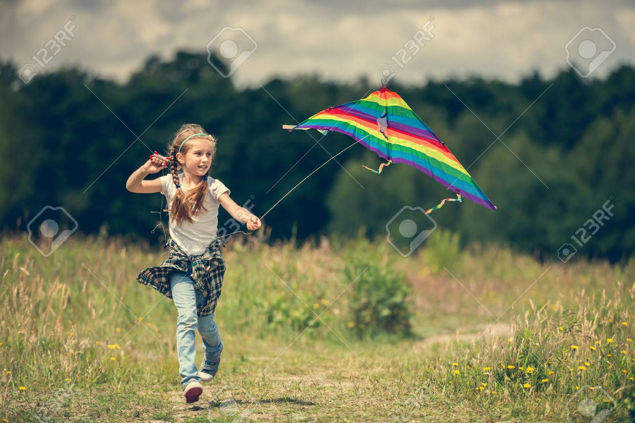little cute girl flying a rainbow kite in a meadow on a sunny day - 44481343