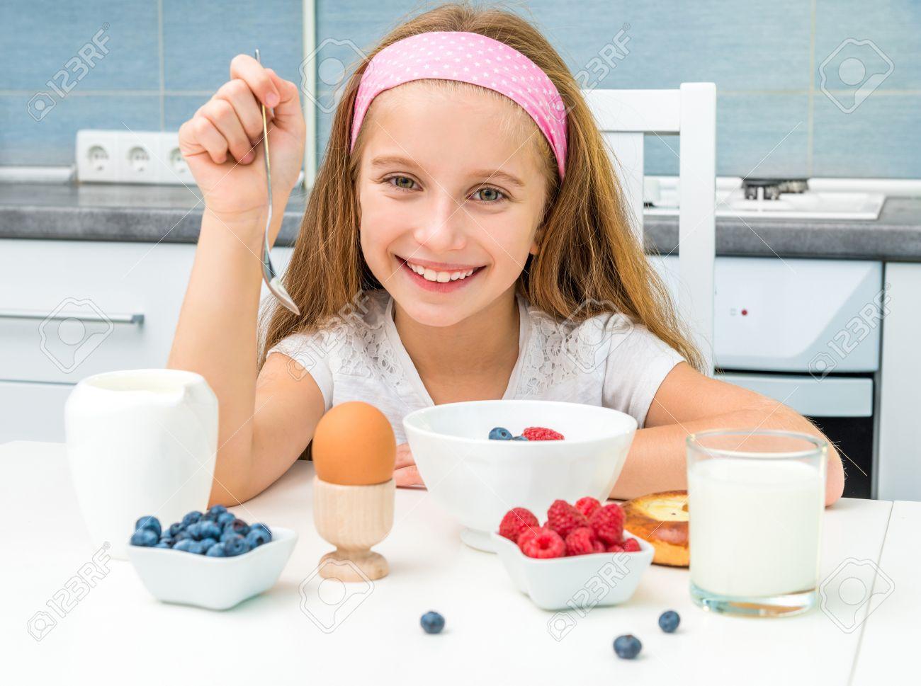 smiling little girl having breakfast - 45297574