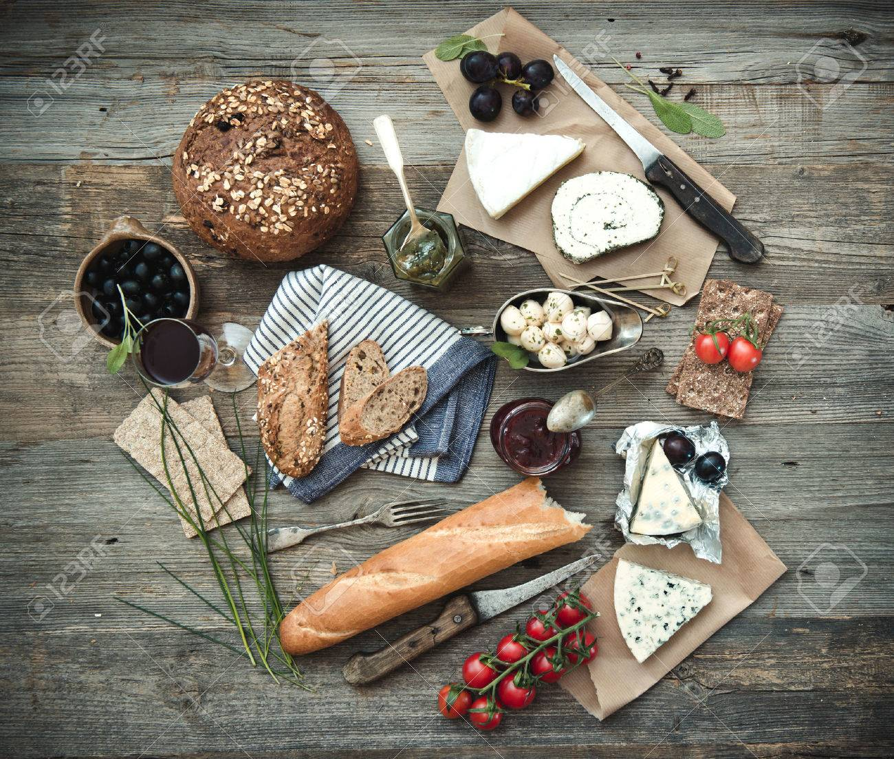 French food on a wooden background. Different types of cheese, wine and other ingredients on a wooden table - 45900264