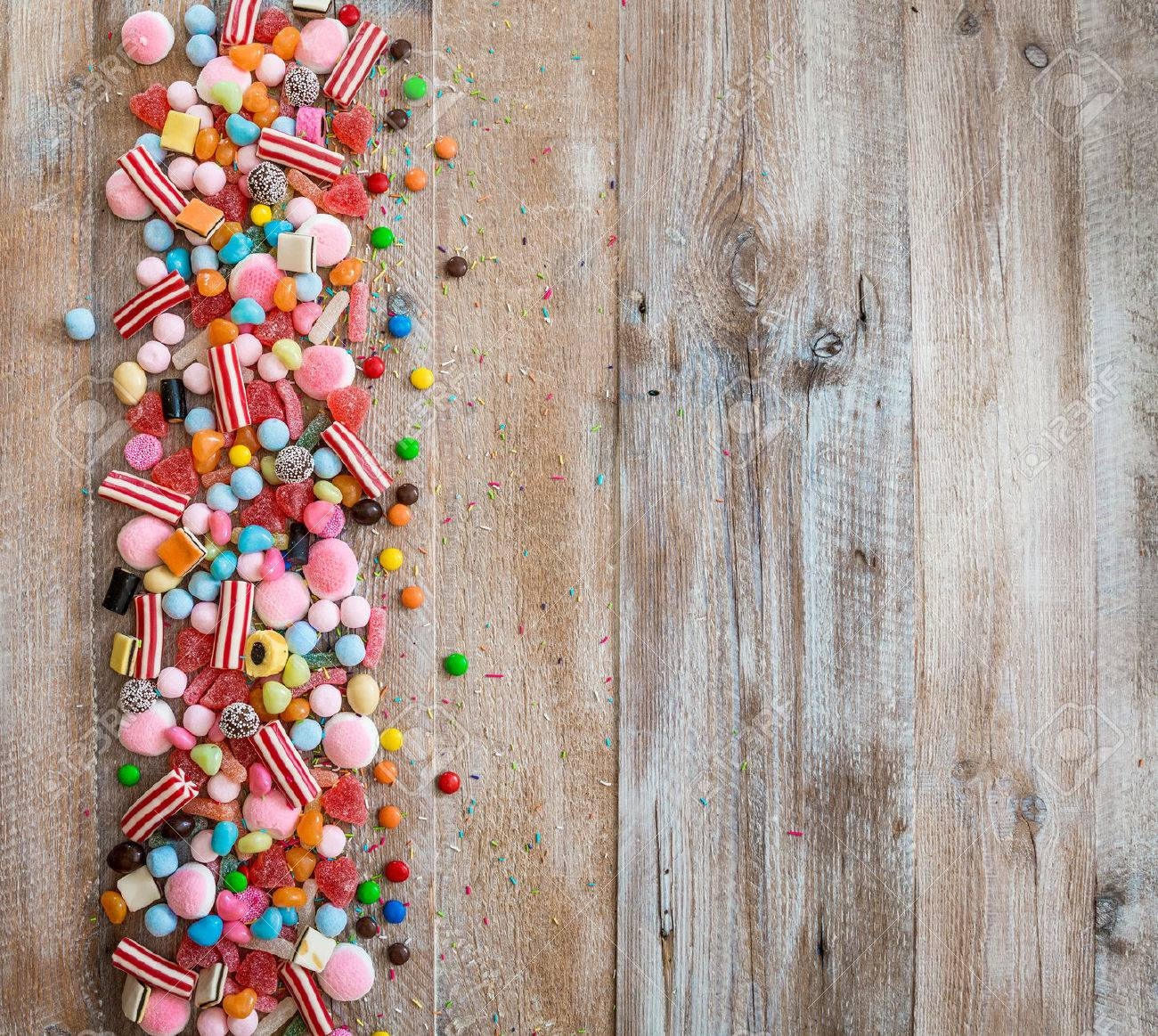 variety of candies on a wooden background with space for text - 46656026