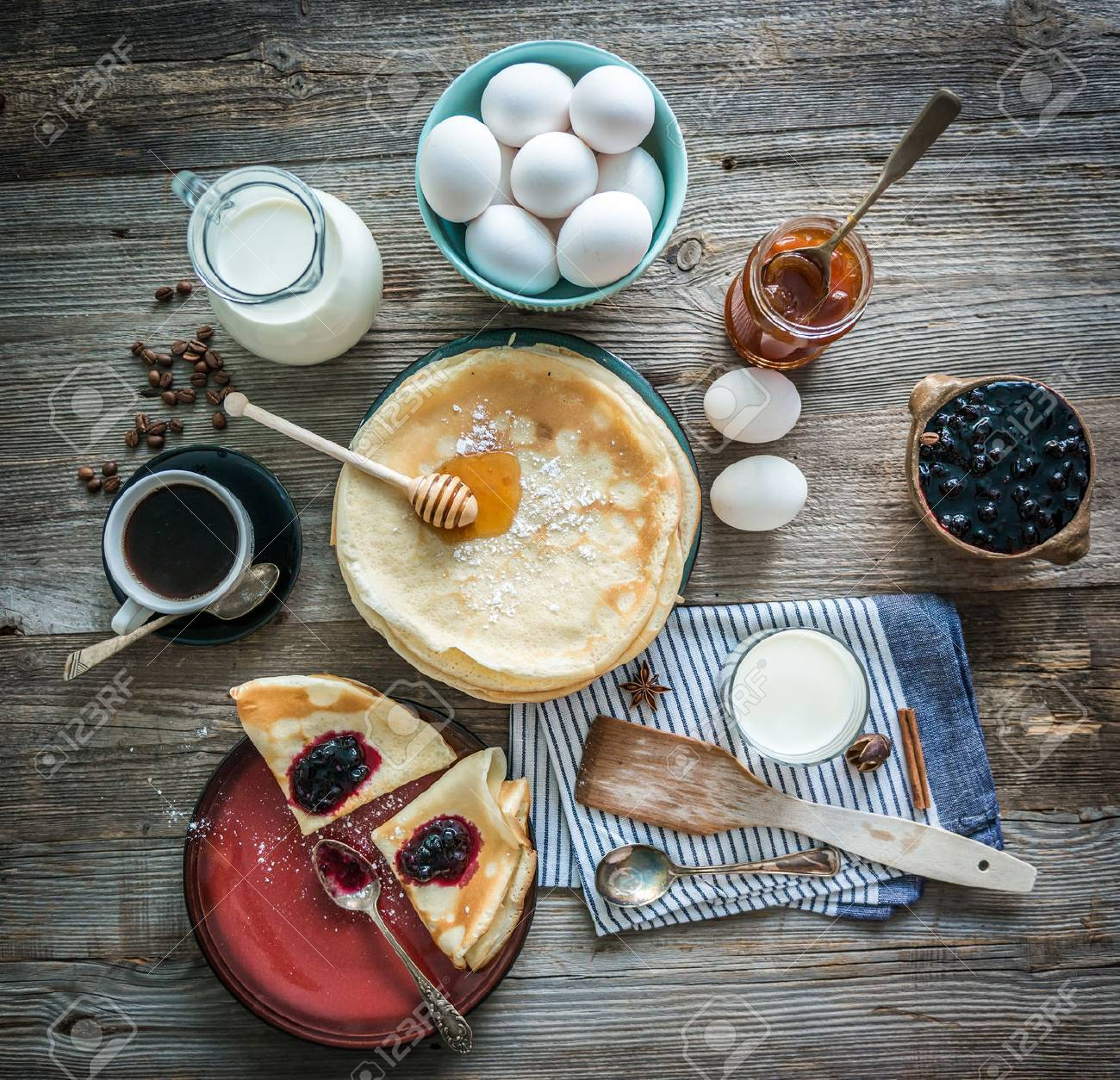 prepared pancakes and coffee among ingredients on wooden background - 47390017