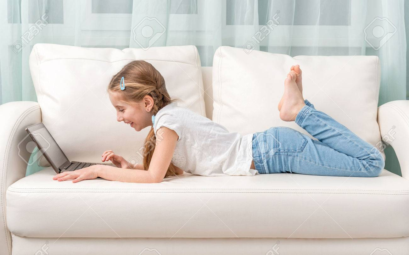 Cute Little Girl Lying On White Sofa Looks At Notebook And Laughs Stock  Photo   57267768