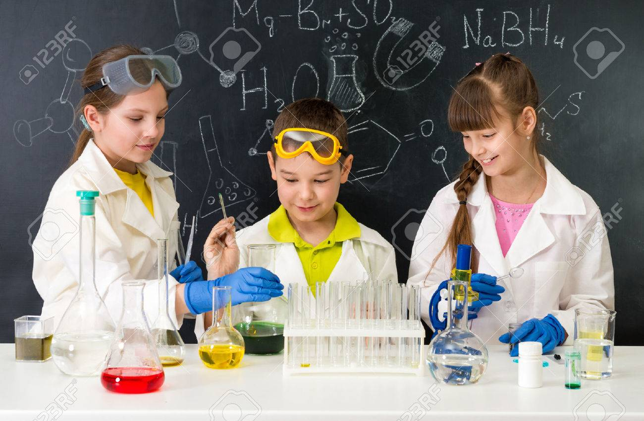 three little students on chemistry lesson in lab doing an experiment - 57342040