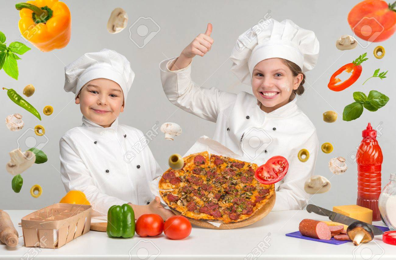 little boy and girl in white uniform of chef by the table with flying pizza - 57342546