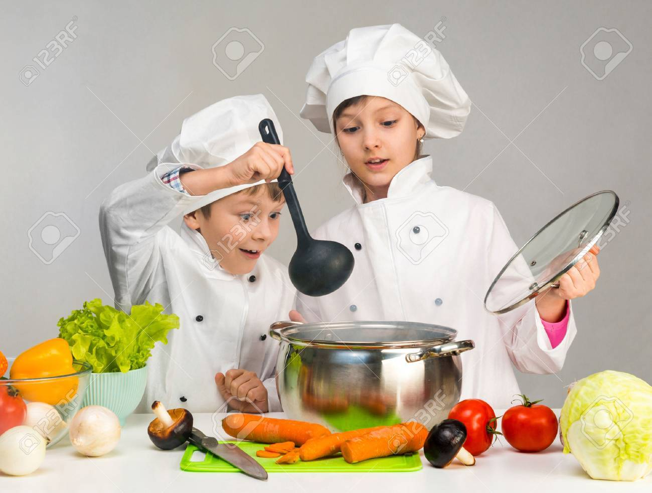 cooking little boy and girl looking in pan on table with vegetables - 61380381