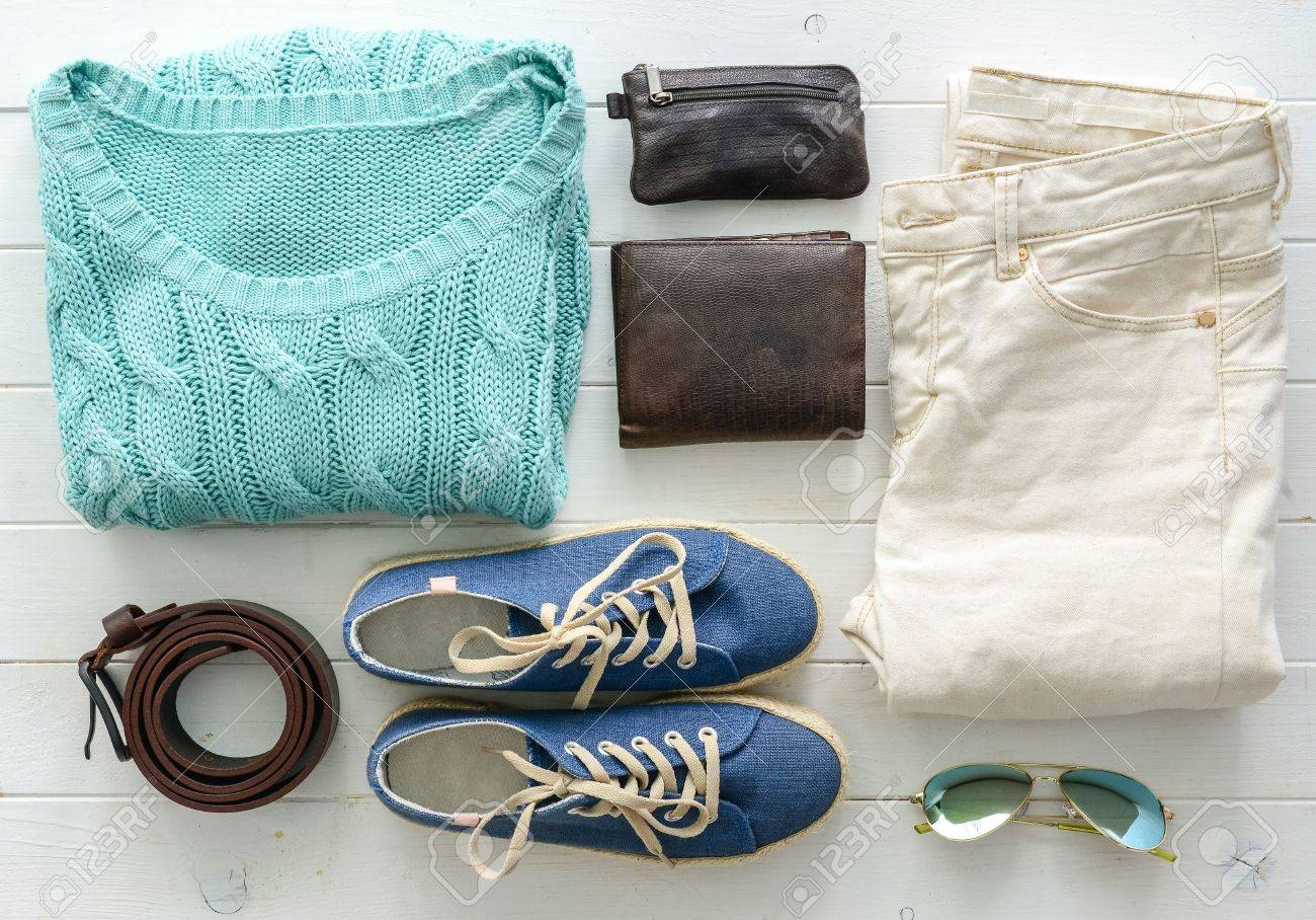 carefully folded woman casual closes and accessories on wooden table top view - 64184765