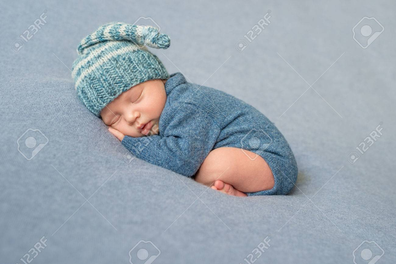 sleeping newborn baby in blue knitted jumpsuit and hat with crossed legs - 64185786