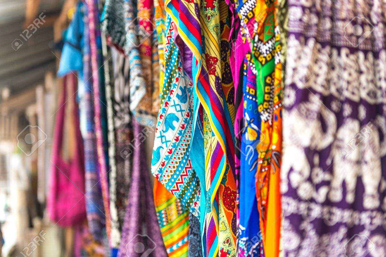 colorful patterned shawls and fabric at Zanzibar traditional street market, Africa - 64186044