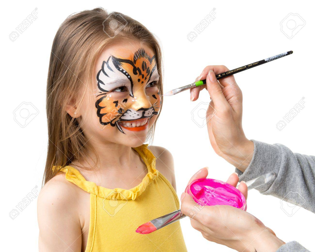 joyful little girl getting her face painted like tiger by artist - 66160250