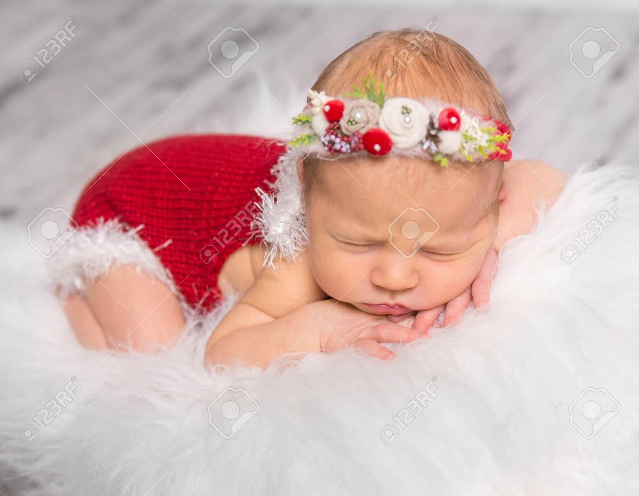 6bd5d5a0b Lovely Newborn Girl In Red Romper And Colorful Headband Sleeping ...
