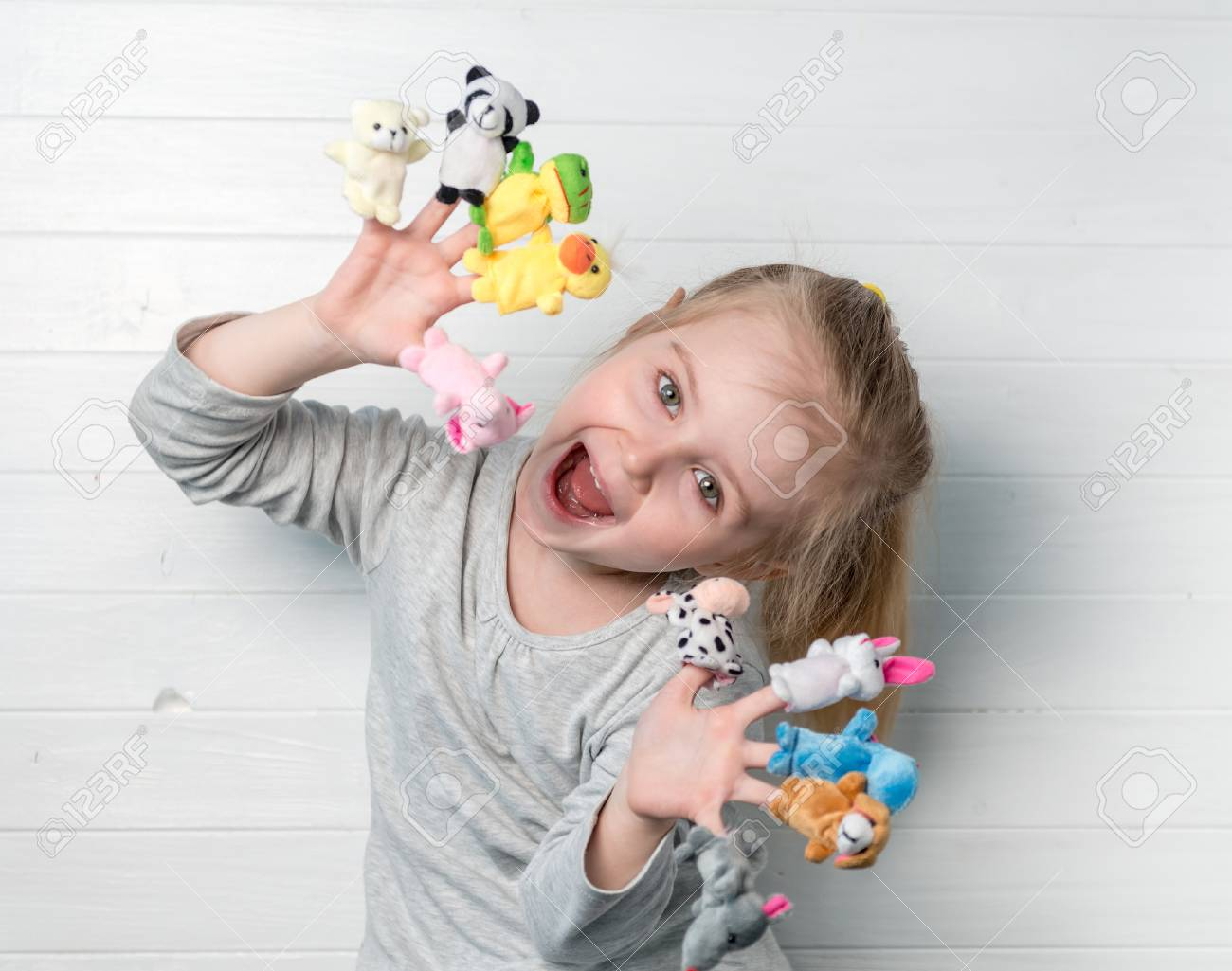 girl with doll puppets on her hands - 76604277