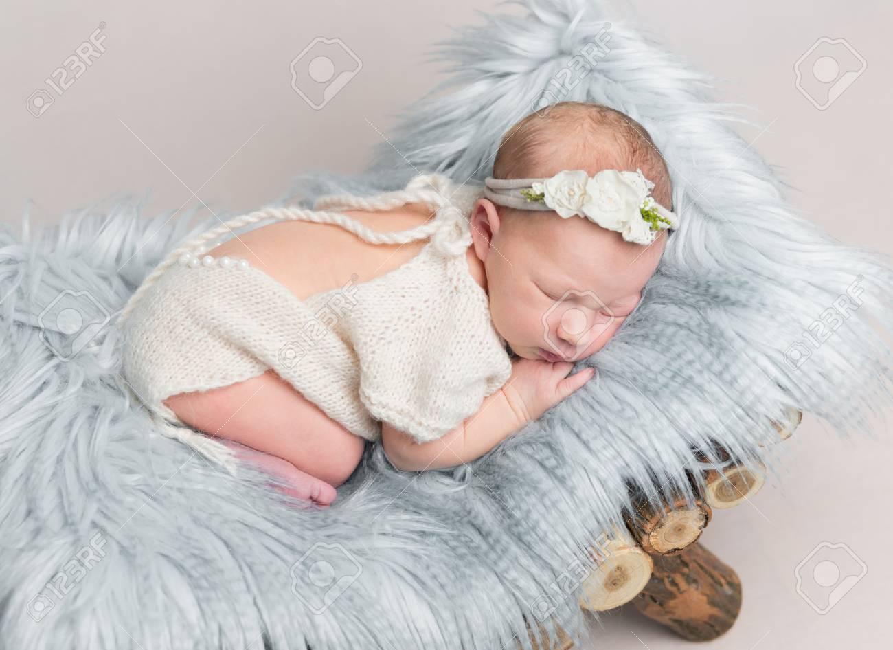 Newborn baby girl sleeps on small wooden crib. - 91187388