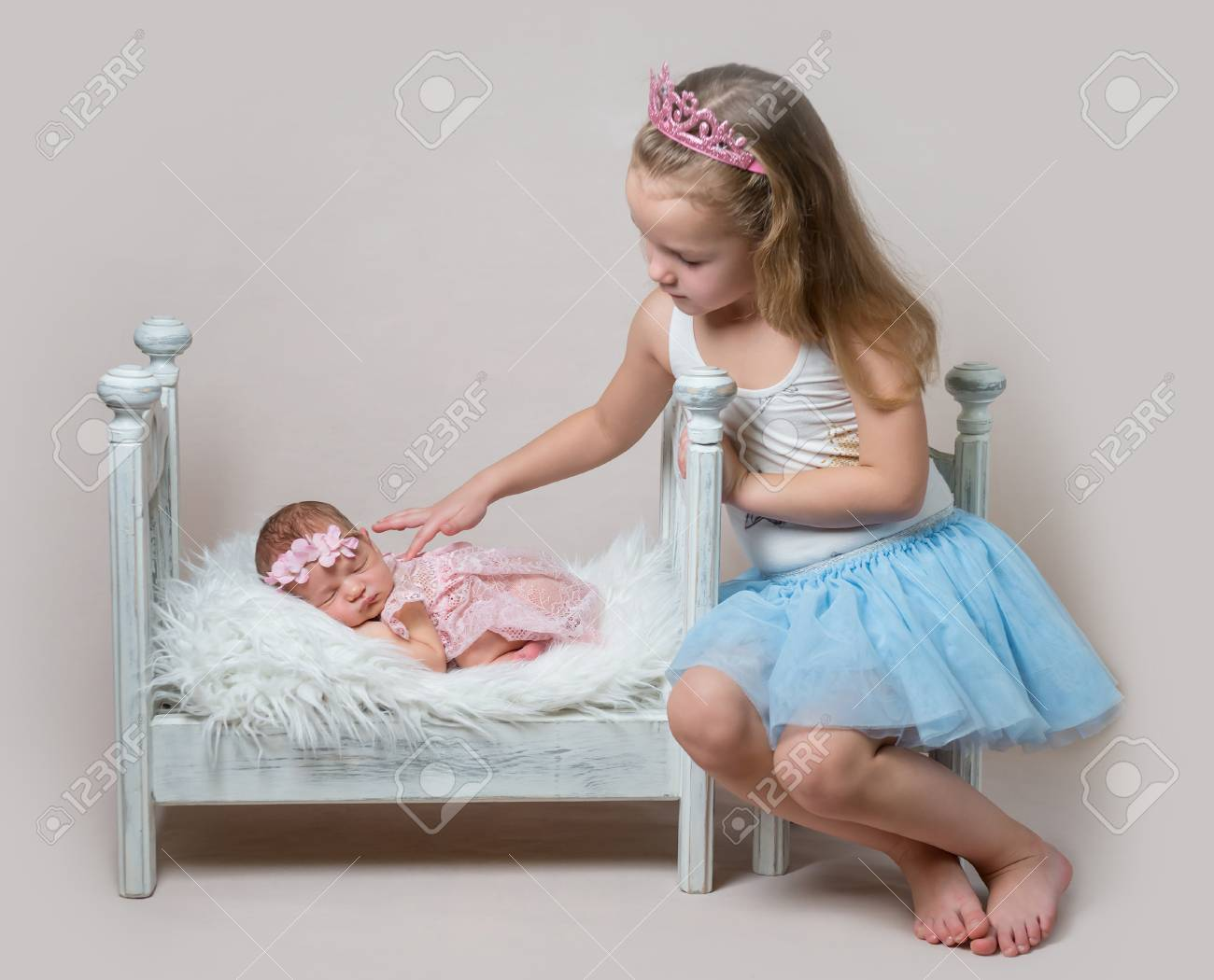 2c4eb35bdd469 Little girl sits next her newborn sister