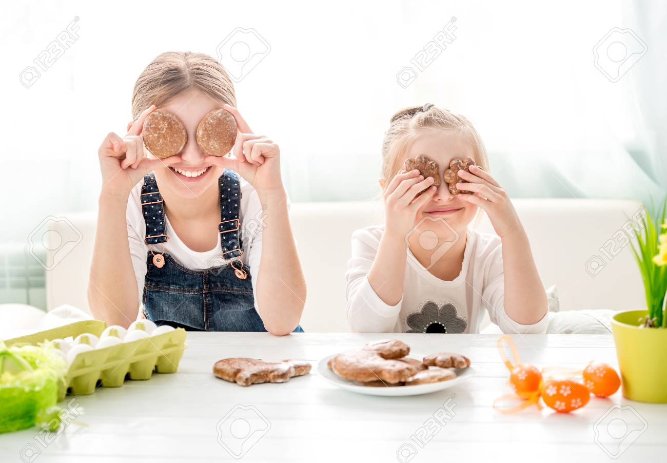 Happy little girls holding Easter cookies in front of their eyes - 102331459