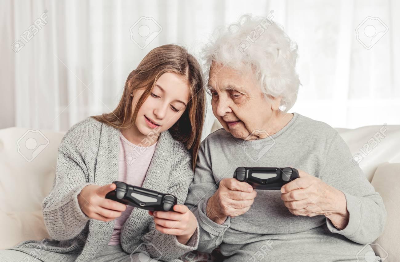 Grandmother with granddaughter playing games - 115999709