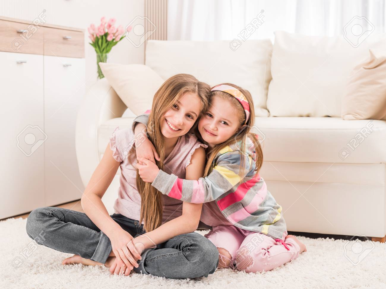 Two sisters sitting in embrace - 118405428